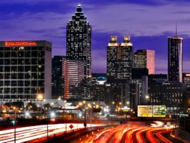 Downtown Atlanta skyline seen past traffic in movement, at dusk